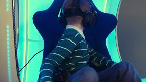 Male child in virtual reality chair enjoying his experience. Professional shot in 4K resolution. 093. You can use it e.g. in your commercial video, business stock video