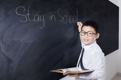 Male child writes text Stay in School Royalty Free Stock Image