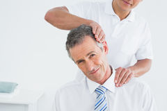 Male chiropractor doing neck adjustment Stock Image