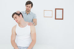 Male chiropractor doing neck adjustment Royalty Free Stock Photography