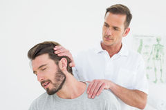 Male chiropractor doing neck adjustment Royalty Free Stock Image