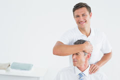 Male chiropractor doing neck adjustment Royalty Free Stock Photo