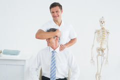 Male chiropractor doing neck adjustment Royalty Free Stock Images