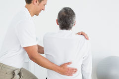 Male chiropractor examining man. Rear view of a male chiropractor examining mature men at office stock photos