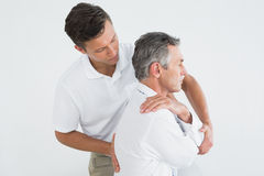 Male chiropractor examining mature man Stock Image