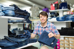 Male chooses jeans at clothing store Royalty Free Stock Images