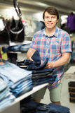 Male chooses jeans at clothing store Royalty Free Stock Image