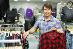 Male choosing shirts in the shop. Young smiling guy choosing shirt at the clothing store Royalty Free Stock Image