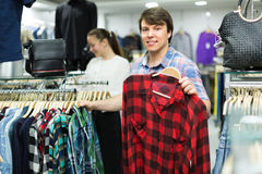 Male choosing shirts in the shop. Young smiling men choosing shirt at the clothing store Royalty Free Stock Images