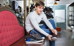 Male choosing summer shoes. Smiling male choosing summer shoes in a shoe shop Royalty Free Stock Images