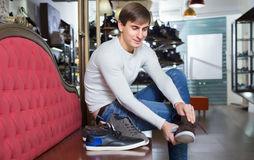 Male choosing summer shoes. Smiling male choosing summer shoes in a shoe shop Stock Photo