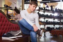 Male choosing summer shoes. Smiling male choosing summer shoes in a shoe store royalty free stock photo