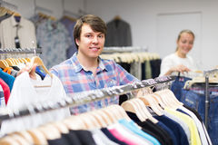 Male choosing t-shirts in the shop. Smiling guy choosing new t-shirt at the clothing store Royalty Free Stock Photo