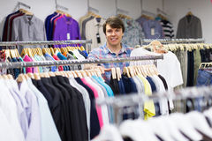 Male choosing t-shirts in the shop. Smiling man choosing t-shirt at the clothing store Royalty Free Stock Image