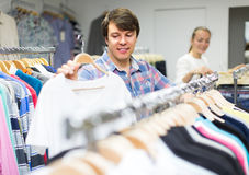 Male choosing t-shirts in the shop. Smiling young men choosing t-shirt at the clothing store Royalty Free Stock Images