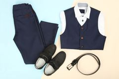 Male classic suit. And accessories on blue and beige background. Concept school uniform Stock Image