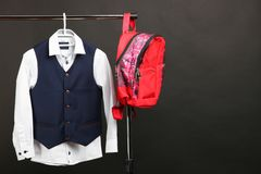 Male classic suit. Male classical suit on hanger and schoolbag on black background. Concept school uniform Stock Images