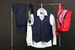 Male classic suit. Male classical suit on hanger and schoolbag on black background. Concept school uniform Royalty Free Stock Photos