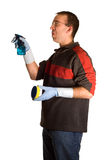 Male Cleaner. A young male wearing rubber gloves, doing some cleaning, isolated against a white background Stock Image