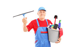 Male cleaner holding a bucket with cleaning supplies and looking Stock Photography