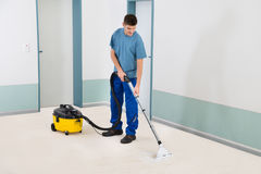 Male Cleaner Vacuuming Floor. Young Male Cleaner In Uniform Vacuuming Floor Stock Photos