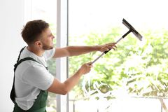 Cleaner wiping window glass with squeegee indoors. Male cleaner wiping window glass with squeegee indoors Royalty Free Stock Images