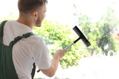 Male cleaner wiping window glass with squeegee. Indoors Royalty Free Stock Image
