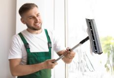 Male cleaner wiping window glass with squeegee. Indoors Stock Image