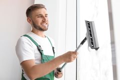 Male cleaner wiping window glass with squeegee. Indoors Stock Photos