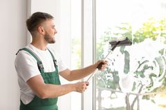 Male cleaner wiping window glass with squeegee. Indoors Royalty Free Stock Photography