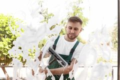 Male cleaner wiping window glass with squeegee. From outside Royalty Free Stock Images