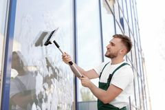 Male cleaner wiping window glass with squeegee. From outside Royalty Free Stock Photography