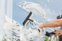 Male cleaner wiping window glass with squeegee. From outside, closeup Stock Image
