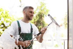 Leaner wiping window glass with squeegee from outside. Male cleaner wiping window glass with squeegee from outside Stock Photo