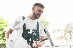 Male cleaner wiping window glass with squeegee. From outside Royalty Free Stock Photos