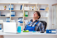 The male cleaner working in the office Stock Photography