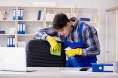 The male cleaner working in the office Royalty Free Stock Photo