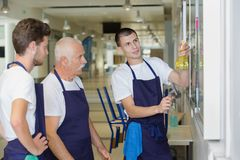 Male cleaning team cleaning notice board. Clean Stock Image