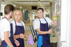 Male cleaning team in discussion. Clean stock photo