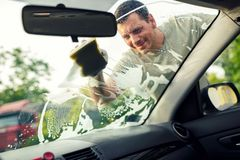 Male is cleaning windows of a car with a sponge and foam. Smiling male is cleaning windows of a car with a sponge and foam Stock Photos