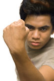 Male clenched closed fist. Masculine clenched closed fist close-up in an aggressive macho gesture, in focus with a blurred determined face in the background Royalty Free Stock Photography