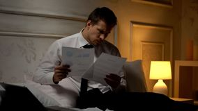 Male clerk preparing report late at night, comparing income of company, diagrams stock image