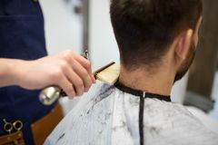 Male client and barber cleaning hair from neck. Grooming, hairdressing and people concept - close up of male client and barber with trimmer and brush cleaning stock photography