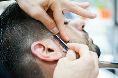 The Barber Male Haircut in Our Days. Male client at the barber shop to have a very modern haircut royalty free stock images