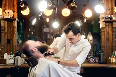 Male client with beard sitting in hairdresser chair. Serious man with long brown beard. Modern popular lumberjack style. royalty free stock photos