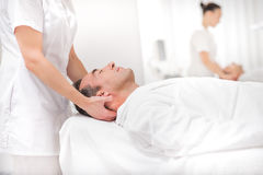 Male client enjoying facial treatment at spa. Middle-aged men is lying on massage table at beauty salon. Masseuse is standing and pampering his head. His eyes Royalty Free Stock Images