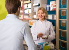 Male client with mature woman pharmacist Royalty Free Stock Image