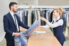 Male client takes a woman Laundry worker clean clothes. Male client takes a women Laundry worker clean clothes at the dry cleaners Stock Photo