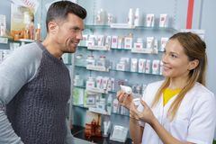 Male client wants to buy cream from professional pharmacist. Male client wants to buy cream from a professional pharmacist Royalty Free Stock Photo