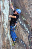 A male climber. A male rock climber clime a stone wall equip with helmet and ropes hanging on a fissure Stock Images
